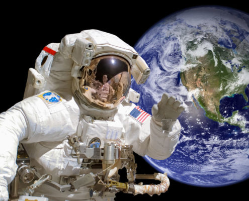 Close up of an astronaut in outer space, earth in the background - elements of this image are provided by NASA